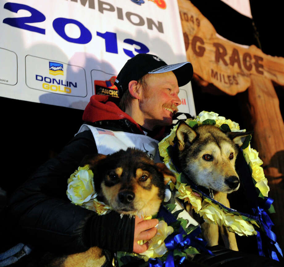 Mitch Seavey became the oldest winner and a two-time Iditarod champion when he drove his dog team under the burled arch in Nome on Tuesday evening, March 12, 2013. Leaders Tanner, left, and Taurus are photographed with Mitch Seavey after wining the dog race. (AP Photo/The Anchorage Daily News, Bill Roth) LOCAL TV OUT (KTUU-TV, KTVA-TV) LOCAL PRINT OUT (THE ANCHORAGE PRESS, THE ALASKA DISPATCH) / The Anchorage Daily News