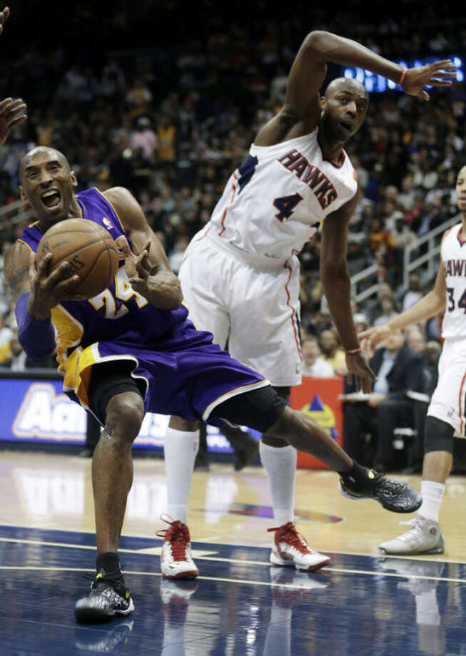 Los Angeles Lakers guard Kobe Bryant (24) comes up with a loose ball in front of Atlanta Hawks forward Anthony Tolliver (4) in the second half of an NBA basketball game in Atlanta Wednesday, March 13, 2013. (AP Photo/John Bazemore)