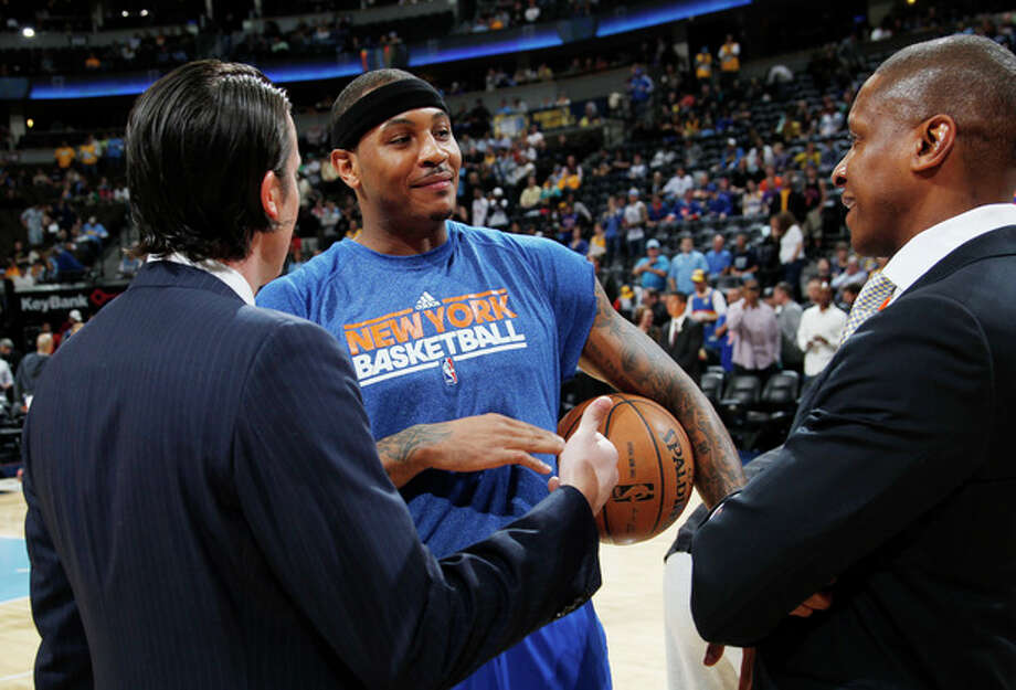 Denver Nuggets President Josh Kroenke, left, talks with New York Knicks forward Carmelo Anthony, center, and Nuggets general manager Masai Ujiri before an NBA basketball game in Denver, Wednesday, March 13, 2013. The game marked Anthony's first at the Pepsi Center after his trade from Denver to New York two years ago. (AP Photo/David Zalubowski) / AP