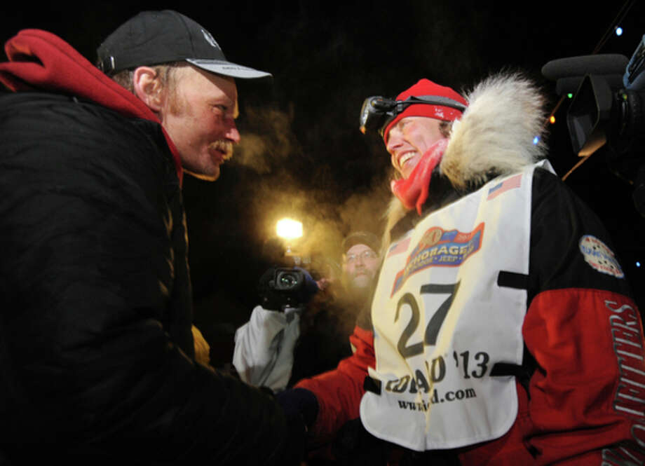 Mitch Seavey became the oldest winner and a two-time Iditarod champion when he drove his dog team under the burled arch in Nome on Tuesday evening, March 12, 2013. He congratulates second place finisher Aliy Zirkle after she arrived in Nome. (AP Photo/The Anchorage Daily News, Bill Roth) LOCAL TV OUT (KTUU-TV, KTVA-TV) LOCAL PRINT OUT (THE ANCHORAGE PRESS, THE ALASKA DISPATCH) / The Anchorage Daily News