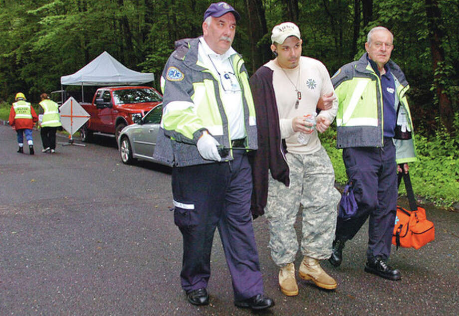 "Gene Scalora and Ron Hitter of the Wilton EMS evacuate simulated victim, Steve Scalora"" while the Wilton Community Emergency Response Team (CERT) conducts a Search and Rescue training exercise at Bradley Park in Wilton on Saturday. CERT holds the training exercise to practice their Search and Rescue skills in the event of a missing person incident. In addition to Wilton CERT, other Wilton Emergency Services and CERT units from Fairfield, Westport, Weston, New Canaan, Stamford and Monroe were in attendance.Hour photo / Erik Trautmann / (C)2012, The Hour Newspapers, all rights reserved"
