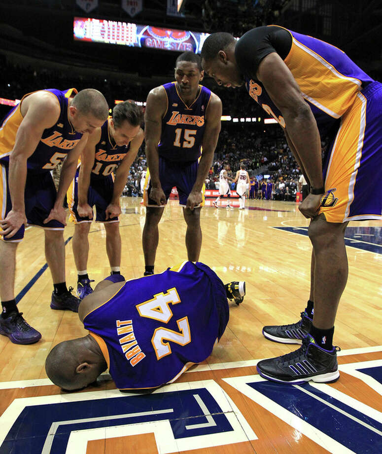 Los Angeles Lakers' Steve Blake, from left, Steve Nash, Metta World Peace and Dwight Howard gather around Kobe Bryant as he lays on the floor after being injured in the final seconds of an NBA basketball game against the Atlanta Hawks on Wednesday, March 13, 2013, in Atlanta. The Hawks defeated the Lakers 96-92. (AP Photo/Atlanta Journal-Constitution, Curtis Compton) / Atlanta Journal-Constitution