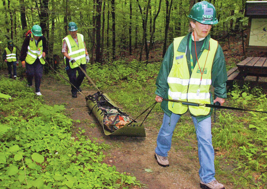CERT volunteer Mary Lou Dunne helps evacuates a simulated victim while the Wilton Community Emergency Response Team (CERT) conducts a Search and Rescue training exercise at Bradley Park in Wilton on Saturday. CERT holds the training exercise to practice their Search and Rescue skills in the event of a missing person incident. In addition to Wilton CERT, other Wilton Emergency Services and CERT units from Fairfield, Westport, Weston, New Canaan, Stamford and Monroe were in attendance.Hour photo / Erik Trautmann / (C)2012, The Hour Newspapers, all rights reserved