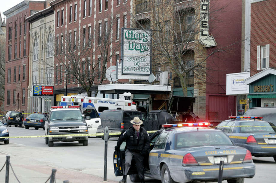 Law enforcement officials work outside the building where a man was killed after police stormed it following a standoff on, Thursday, March 14, 2013, in Herkimer, N.Y. Kurt Myers, 64, was suspected of two shootings on Wednesday that killed four and injured two others. (AP Photo/Mike Groll) / AP