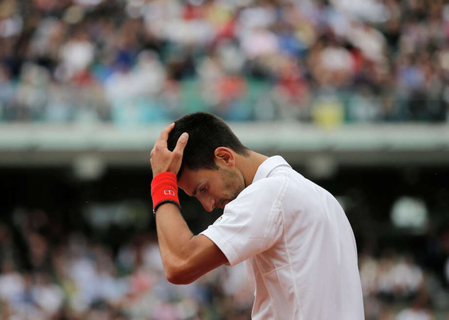 Serbia's Novak Djokovic holds his head as he plays France's Jo-Wilfired Tsonga during their quarterfinal match in the French Open tennis tournament at the Roland Garros stadium in Paris, Tuesday, June 5, 2012. (AP Photo/Christophe Ena) / AP