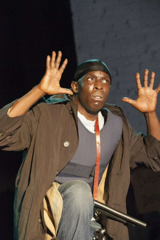 "This image from video released by Funny or Die, actor Michael Kenneth Williams, best known as Omar Little in the HBO series, ""The Wire,"" reprises his role for the comedy video ""The Wire: The Musical."" The video appears as a four-minute commercial that advertises comically sunny songs like ""Omar's Comin,'"" ""It's All in the Game"" and ""I'm Just a Burner"" _ a sad lament from one of the disposable cellphones used by the drug dealers on the show. (AP Photo/Funny or Die)"