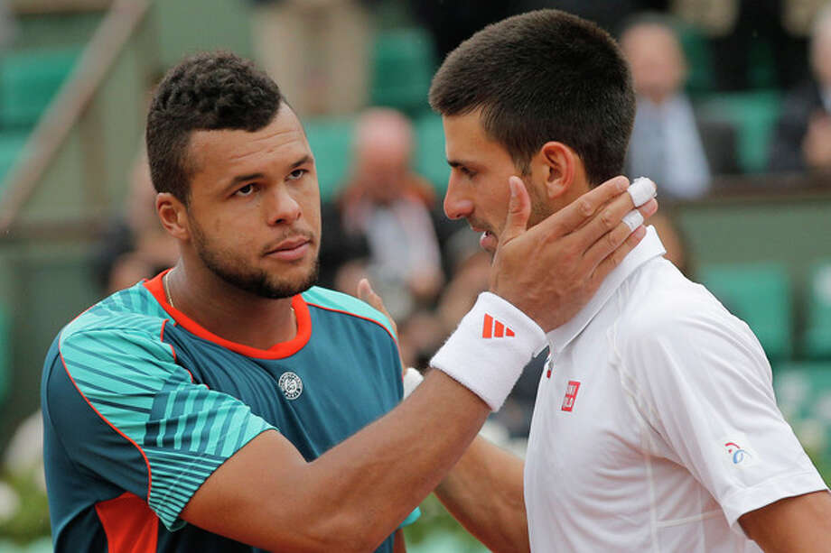 Jo-Wilfried Tsonga of France, left, congratulates Novak Djokovic of Serbia after losing his quarter final match at the French Open tennis tournament in Roland Garros stadium in Paris, Tuesday June 5, 2012. Djokovic won in five sets 6-1, 5-7, 5-7, 7-6, 6-1. (AP Photo/Christophe Ena) / AP
