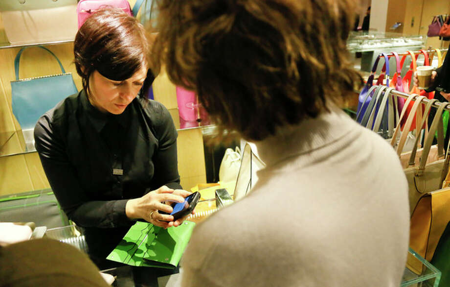 In this Friday, Feb. 15, 2013, photo, a sales staff member at Barney's New York uses an iPod Touch to help a customer make a purchase, in New York. Stores across the country are ditching the old-fashioned, clunky cash registers and instead having salespeople _ and shoppers themselves _ checkout on smartphones and tablet computers. (AP Photo/Bebeto Matthews) / AP
