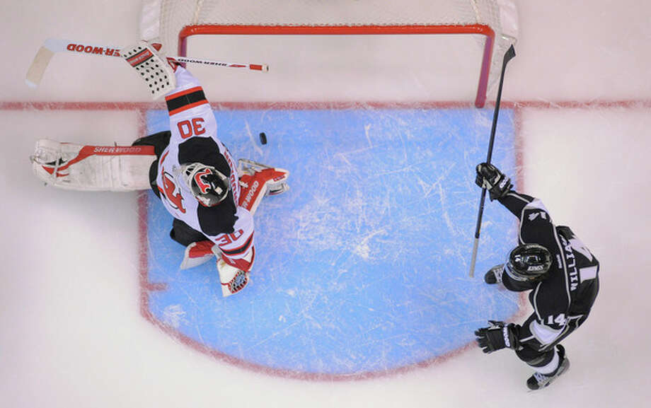 The puck slips past New Jersey Devils goalie Martin Brodeur (30) for a goal as Los Angeles Kings right wing Justin Williams (14) looks on in the second period during Game 3 of the Stanley Cup Finals, Monday, June 4, 2012, in Los Angeles. (AP Photo/Mark J. Terrill) / AP