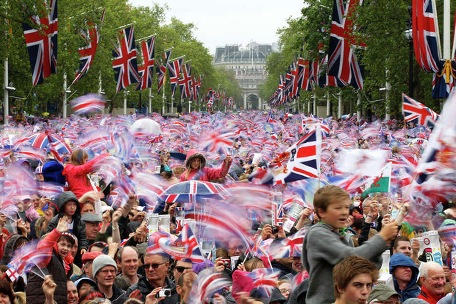 Revelers on the Mall in London watch Britain Queen Elizabeth II appear on the Buckingham Palace balcony as part of a four-day Diamond Jubilee celebration to mark the 60th anniversary of Queen Elizabeth II accession to the throne, Tuesday, June 5, 2012. (AP Photo/Sang Tan) / AP