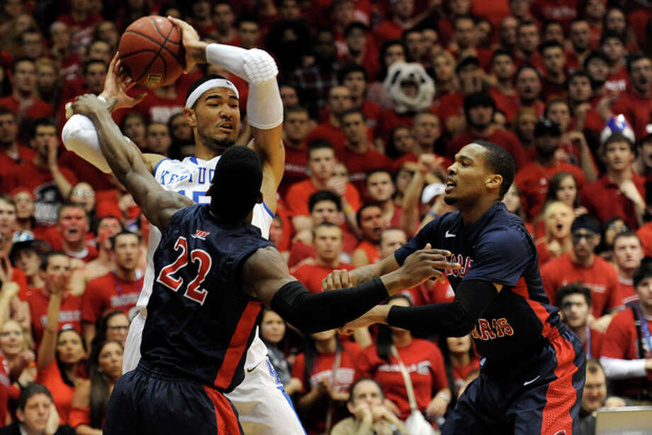 Kentucky forward Willie Cauley-Stein (15) looks to pass as Robert Morris forward Lucky Jones (22) and Mike McFadden defend during the first half of an NIT college basketball game on Tuesday, March 19, 2013, in Coraopolis, Pa. (AP Photo/Don Wright) / FR87040 AP