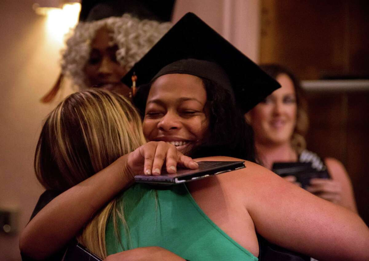 Damelfri Hernandez gives a teary hug after getting her diploma at Bullard-Havens Technical High School commencement, held at the Klein Memorial Auditorium, in Bridgeport, Conn. on Tuesday, June 14, 2016.