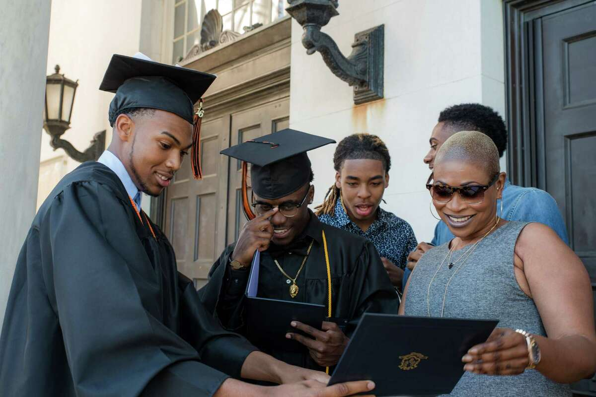 From left, Daiwon Nelson and Azonte Craddock show off their diplomas to Jamaul Wynter, Horace Edwards, and Shelleann Nelson after Bullard-Havens Technical High School commencement, held at the Klein Memorial Auditorium, in Bridgeport, Conn. on Tuesday, June 14, 2016.