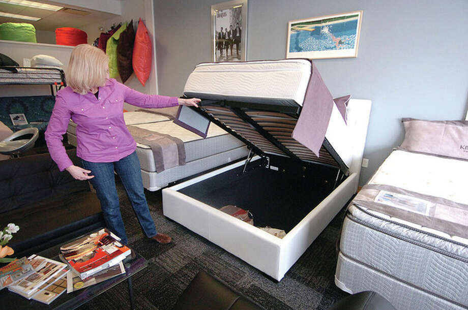 Hour Photo/Alex von Kleydorff. Erin Babrowicz shows the 20sq ft of storage under the full size European style bed in their store, Affordable Mattress and Furniture at 608 West Ave Norwalk / 2013 The Hour Newspapers