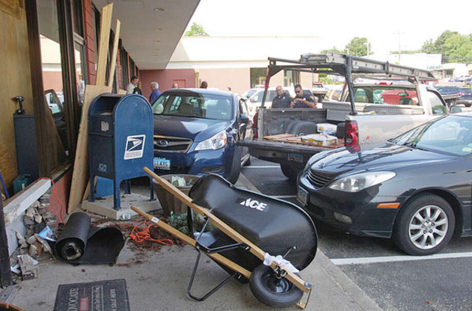 A man driving a Suburu crashed into the front of the County Mall on Westport Ave. striking a worker with Sedona Real Estate Group. / (C)2011, The Hour Newspapers, all rights reserved