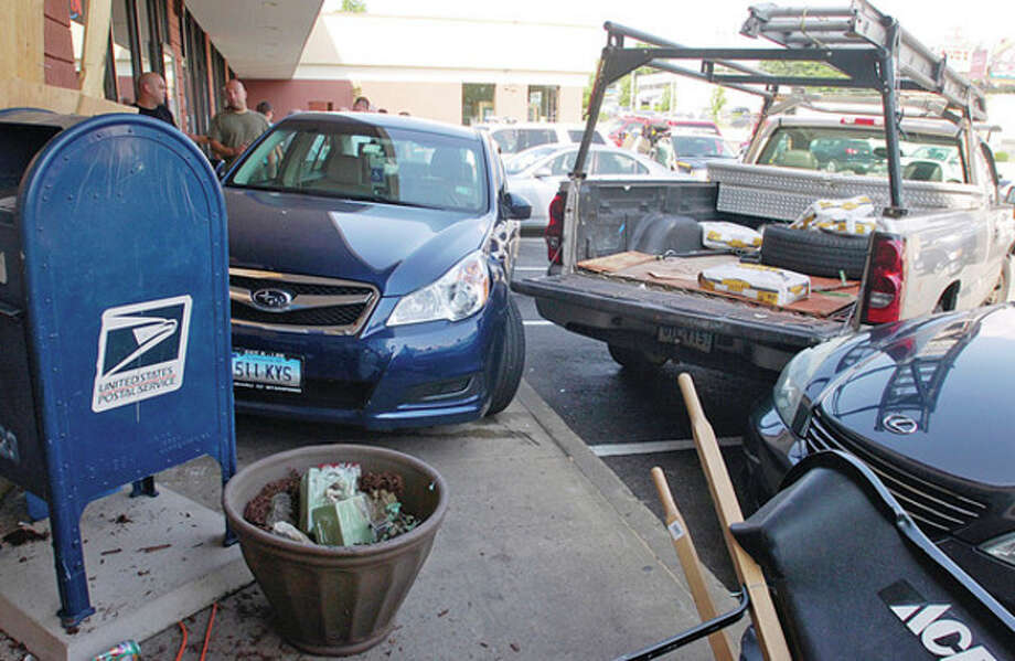 A man driving a Suburu crashed into the front of a store at the County Mall on Westport Ave. Tuesday striking a worker with Sedona Real Estate Group. / (C)2011, The Hour Newspapers, all rights reserved