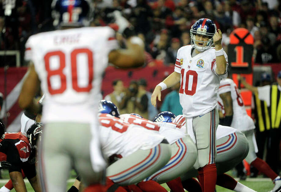 New York Giants quarterback Eli Manning (10) speaks to Giants wide receiver Victor Cruz (80) against the Atlanta Falcons during the first half of an NFL football game on Sunday, Dec. 16, 2012, in Atlanta. (AP Photo/John Amis) / FR69715 AP