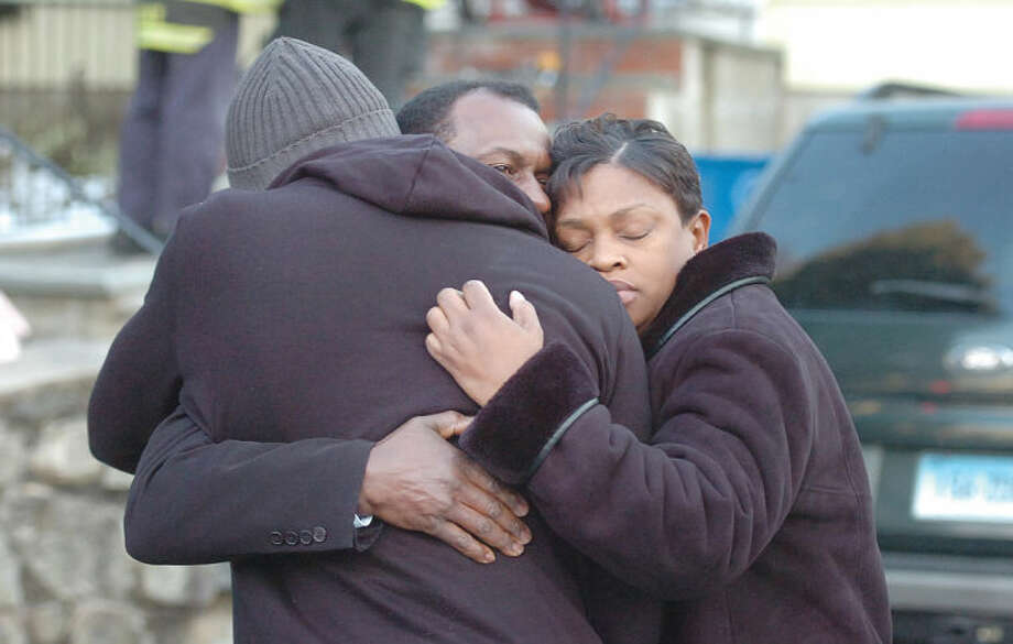 Hour Photo/Alex von Kleydorff. Paul Stevens who was pulled from the second floor window of the burning house, gets a hug from his mother Kathy Burgess and another person after Norwalk Fire Department responded to the home on Leuvine St. and rescued him and put out the fire.