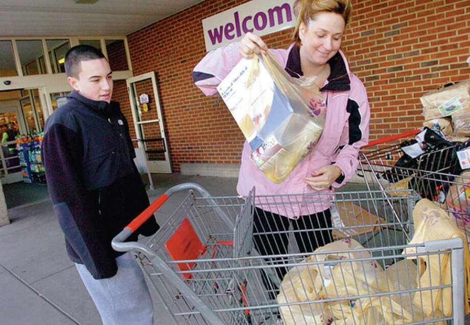 "Hour photo / Erik Trautmann Norwalk resident Tari Dul donates food to the BMHS Senators Community Foundation's ""Fill The Bus"" Program at Super Stop & Shop on Connecticut Avenue Saturday while foundation member Brendan Mills looks on. The foundation donates the items from the food drive to needy families in Norwalk for the holidays. / (C)2011, The Hour Newspapers, all rights reserved"