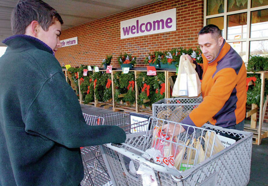 Norwalk resident Keith Harper donates food to the BMHS Senators Community Foundation's Fill The Bus Program at Super Stop and Shop on CT Ave Saturday while foundation member Chris Gatt looks on. The foundation donates the food to needy families in Norwalk for the holidays. Hour photo / Erik Trautmann / (C)2011, The Hour Newspapers, all rights reserved