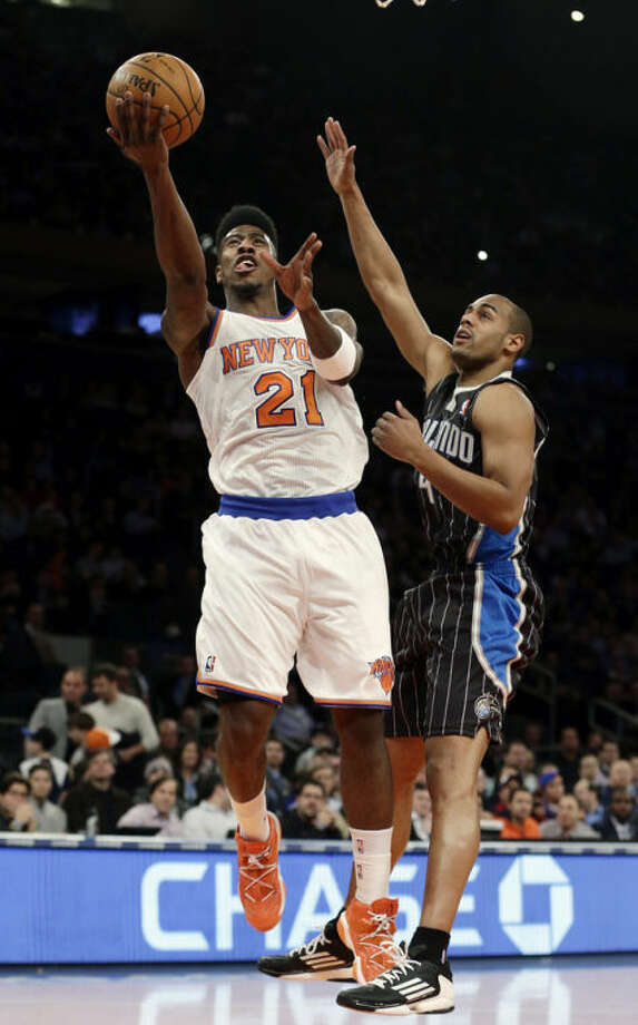 New York Knicks' Iman Shumpert (21) drives past Orlando Magic's Arron Afflalo (4) during the first half of an NBA basketball game, Wednesday, March 20, 2013, in New York. (AP Photo/Frank Franklin II)