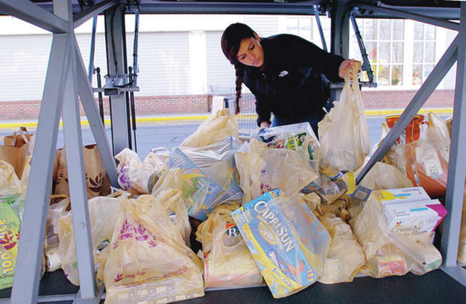 BMHS Senators Community Foundation member Gillian Castro loads up donated food for their Fill The Bus Program at Super Stop and Shop on CT Ave Saturday. The foundation donates the items from the food drive to needy families for in Norwalk the holidays. Hour photo / Erik Trautmann / (C)2011, The Hour Newspapers, all rights reserved