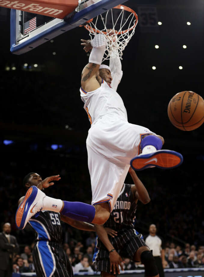New York Knicks' Kenyon Martin dunks the ball in front of Orlando Magic's E'Twaun Moore (55) and Moe Harkless (21) during the first half of an NBA basketball game, Wednesday, March 20, 2013, in New York. (AP Photo/Frank Franklin II)