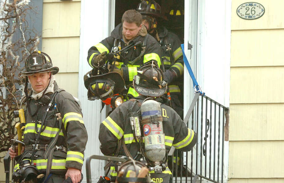 Hour Photo/Alex von Kleydorff. Norwalk Firefighters respond to a fire on Leuvine St Wednesday evening, where a man was rescued from the second floor using a ladder