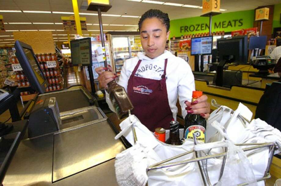 Photo/Alex von Kleydorff. Cashier Shante Vines packs some groceries into plastic bags at Compare Foods in SONO.