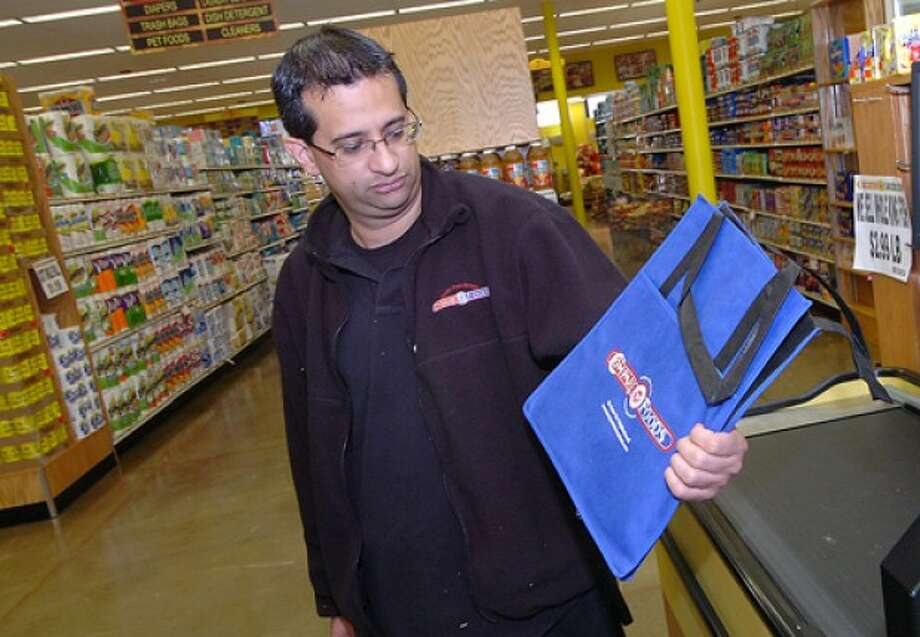 Photo/ Alex von kleydorff. Store manager Carlos Pena holds a reusable grocery bag he offers to his customers at Compare Foods in SONO