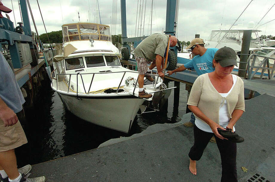 Photo by Alex von Kleydorff. Wilton's Claudia and Tom Bennett step off the bow of their 48-foot Sea Ranger Trawler, 'Another Fetish,' as a crew at Norwalk's Cove Marina lift it out of the water as hurricane Irene makes its way to New England. / 2011 The Hour Newspapers
