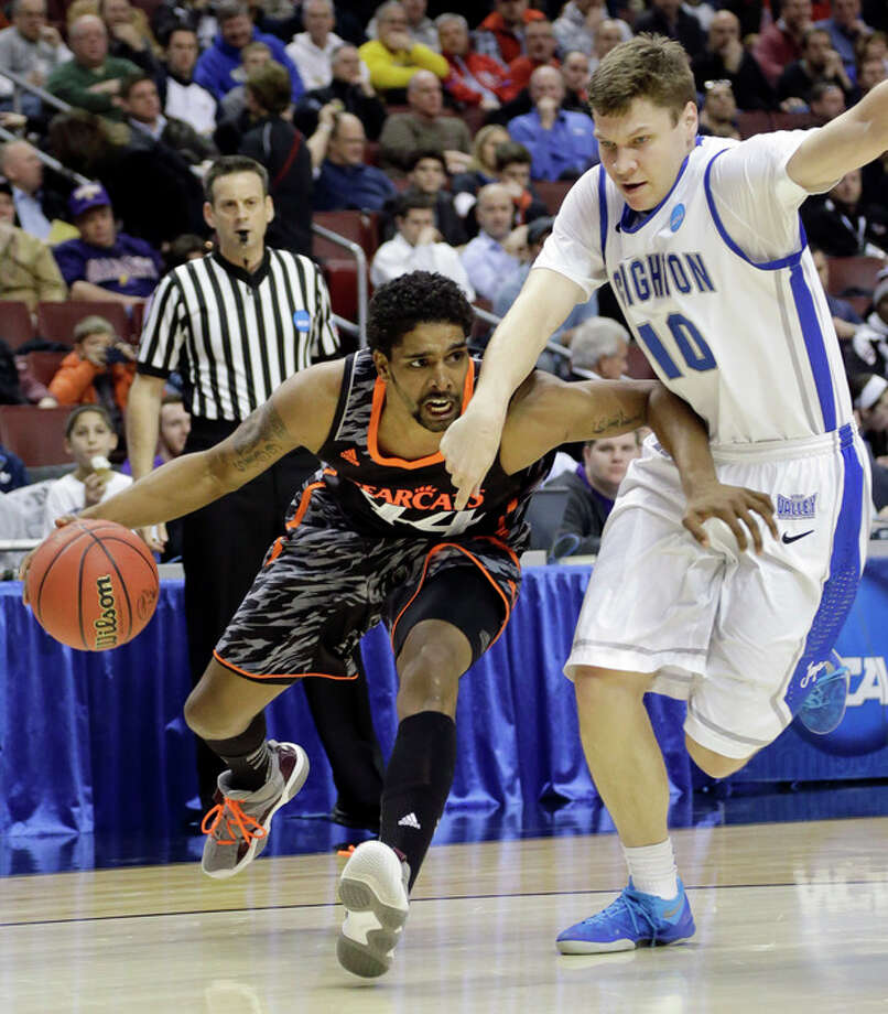 Cincinnati's JaQuon Parker, left, dribbles past Creighton's Grant Gibbs during the first half of a second-round game of the NCAA college basketball tournament, Friday, March 22, 2013, in Philadelphia. (AP Photo/Matt Slocum) / AP