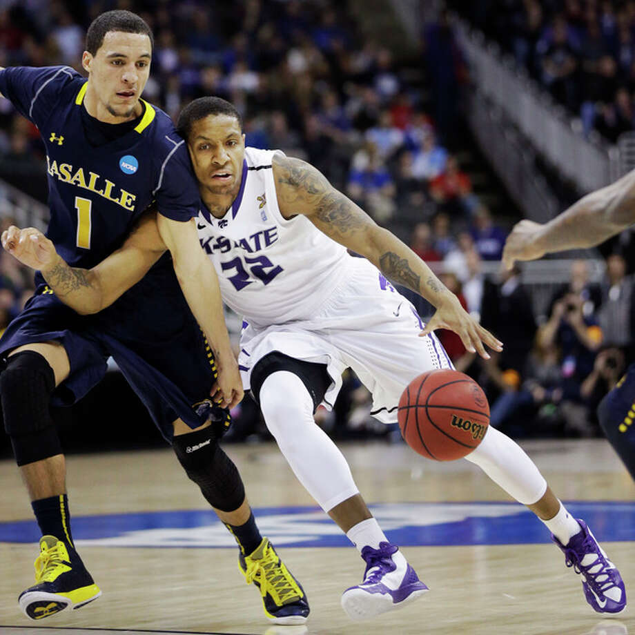 Kansas State guard Rodney McGruder (22) drives on La Salle guard D.J. Peterson (1) during the first half of a second-round game in the NCAA college basketball tournament at the Sprint Center in Kansas City, Mo., Friday, March 22, 2013. (AP Photo/Orlin Wagner) / AP