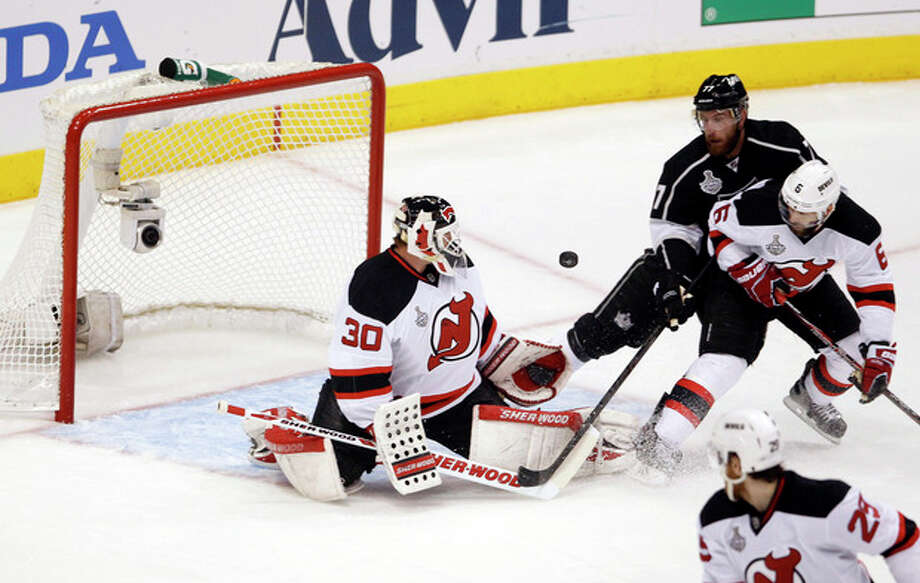 New Jersey Devils' Martin Brodeur stops a shot of goal as Los Angeles Kings' Jeff Carter (77) and New Jersey Devils' Andy Greene (6) approach in the first period during Game 4 of the NHL hockey Stanley Cup finals, Wednesday, June 6, 2012, in Los Angeles. (AP Photo/Jae C. Hong) / AP
