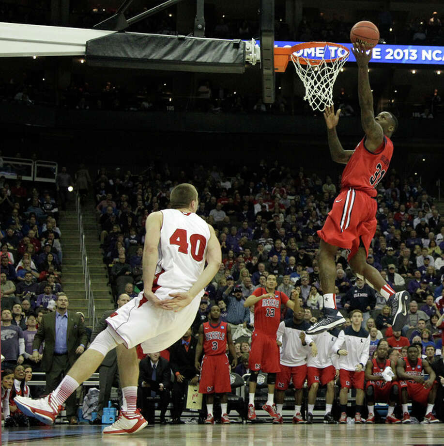 Mississippi forward Murphy Holloway (31) gets past Wisconsin forward/center Jared Berggren (40) to score during the second half of a second-round game of the NCAA college basketball tournament Friday, March 22, 2013, in Kansas City, Mo. Mississippi won 57-46. (AP Photo/Charlie Riedel) / AP