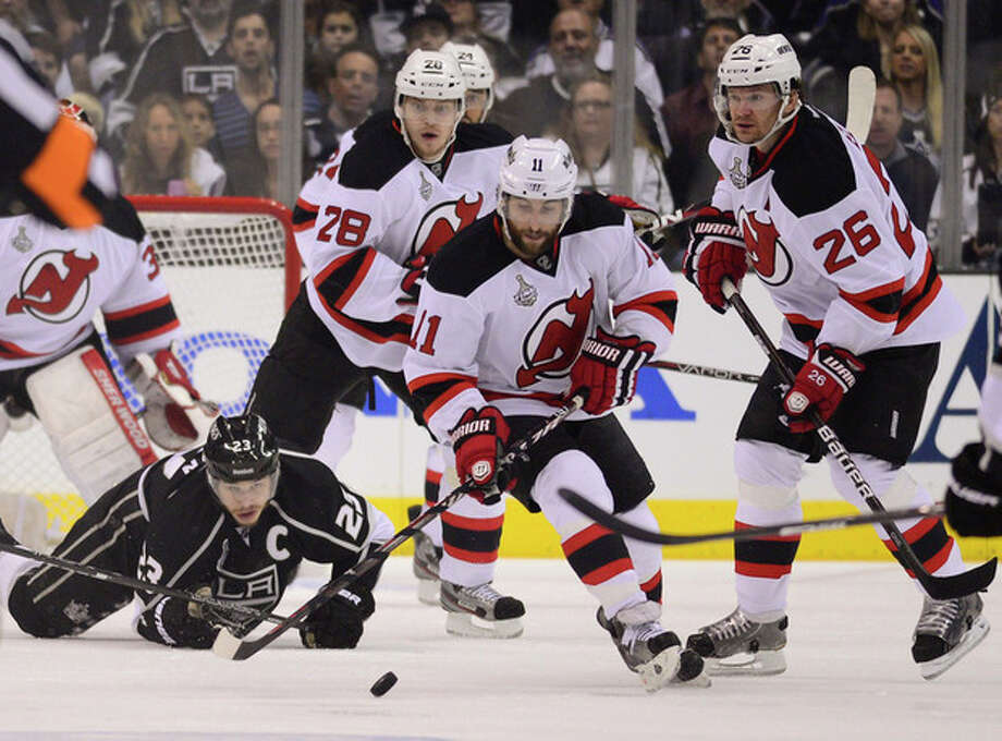 New Jersey Devils' Stephen Gionta (11)guides the puck away as Los Angeles Kings' Dustin Brown (23) watches in the first period during Game 4 of the NHL hockey Stanley Cup finals, Wednesday, June 6, 2012, in Los Angeles. New Jersey Devils' Anton Volchenkov, of Russia, (28) and Patrik Elias, of Czech Republic, were nearby. (AP Photo/Mark J. Terrill) / AP