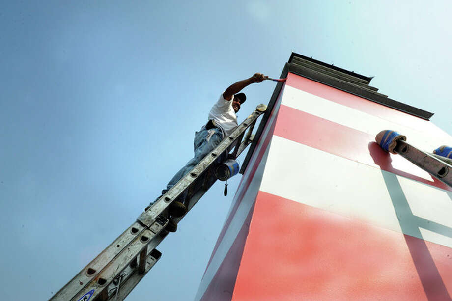 Hour photo/Matthew Vinci A painter works high up on a ladder Thursday at the Stepping Stones Museum for Children. Temperatures were around 90 degrees in the late afternoon.
