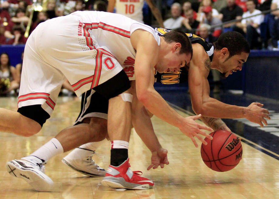 Ohio State guard Aaron Craft, left, chases a loose ball with Iona guard Tre Bowman in the first half of a second-round game at the NCAA college basketball tournament, Friday, March 22, 2013, in Dayton, Ohio. (AP Photo/Skip Peterson) / FR23879 AP