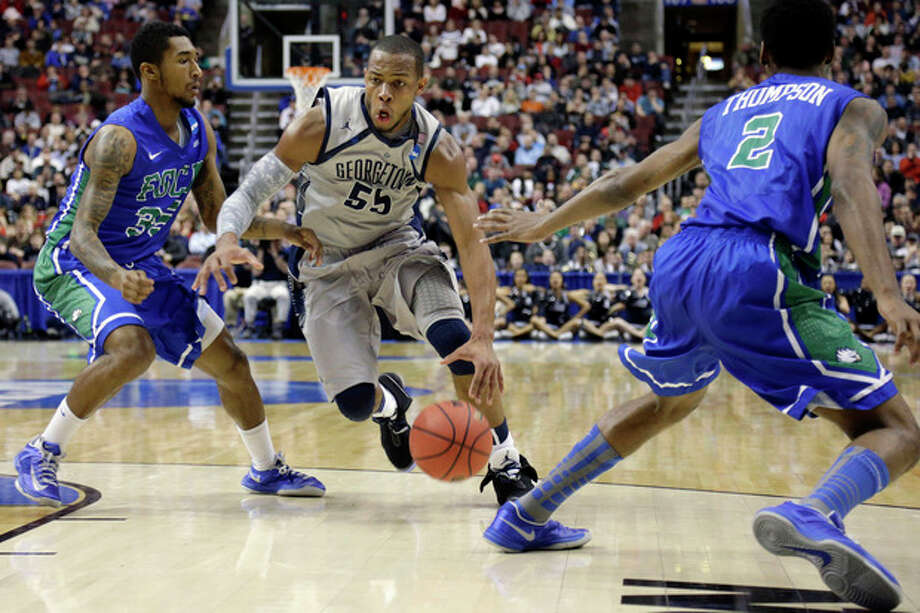Georgetown's Jabril Trawick, center, dribbles between Florida Gulf Coast's Dajuan Graf, left, and Bernard Thompson during the first half of a second-round game of the NCAA college basketball tournament on Friday, March 22, 2013, in Philadelphia. (AP Photo/Matt Rourke) / AP