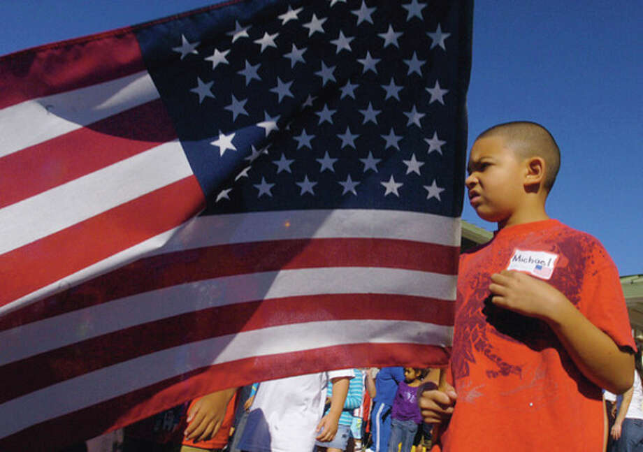 Second grader and student council member Michael Lopez holds the american flag during a 9/11 commemoration ceremony at Fox Run School Friday. / (C)2011, The Hour Newspapers, all rights reserved