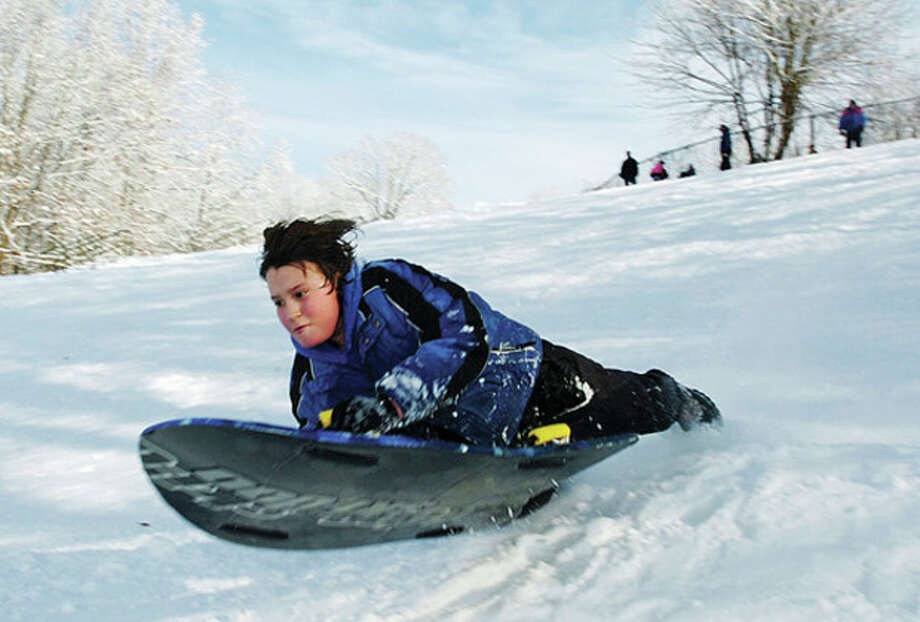 Matthew Clarke, 11, hits a jump while sledding at Wolfpit Elementary School in Norwalk on Saturday. Hour photo / Erik Trautmannon Saturday. Hour photo / Erik Trautmann / (C)2010 The Hour