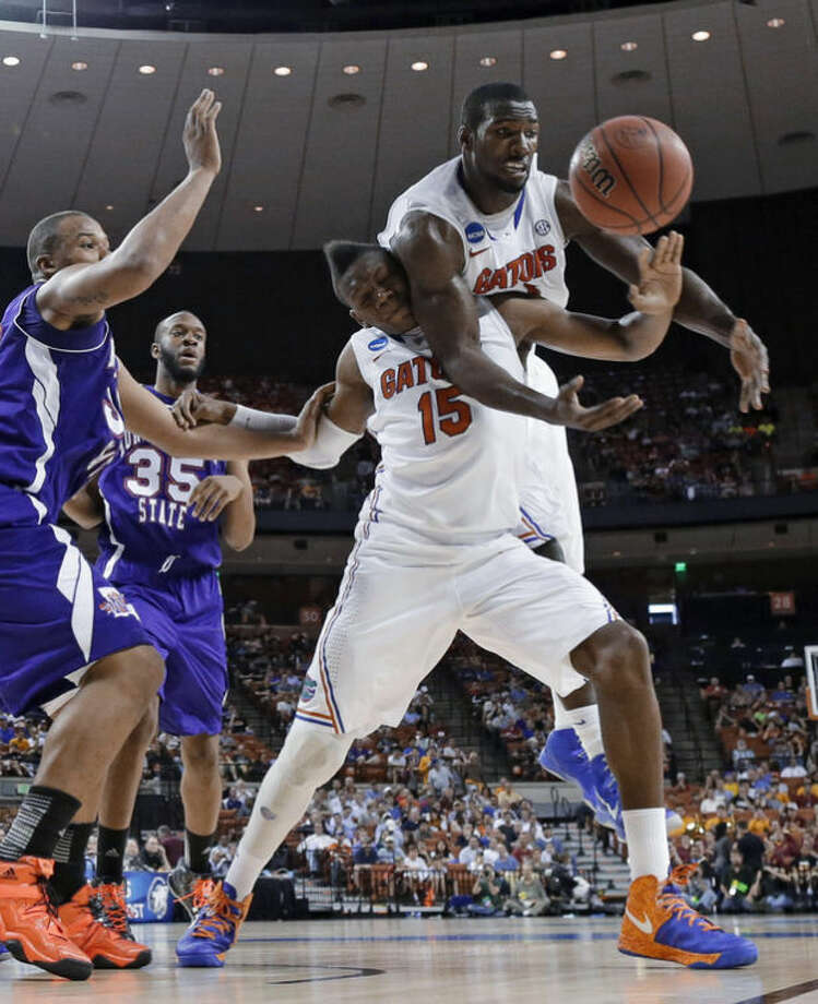 Florida's Patric Young, right, reaches over teammate Will Yeguete (15) while chasing a rebound along with Northwestern State's DeQuan Hicks, left, during the first half of a second-round game of the NCAA men's college basketball tournament Friday, March 22, 2013, in Austin, Texas. (AP Photo/David J. Phillip)