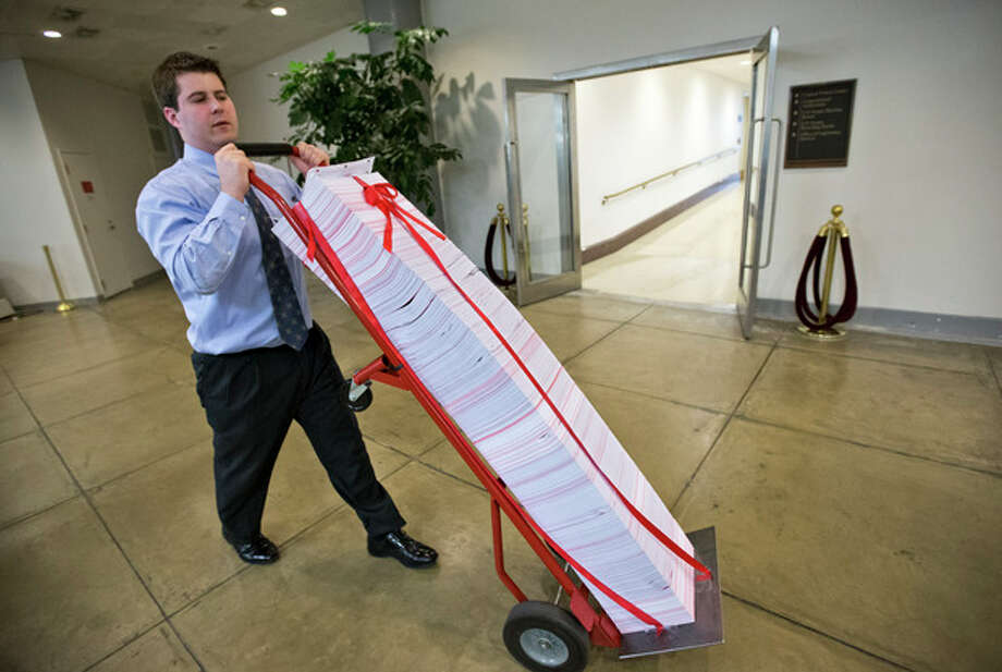 "A Senate aide delivers a stack of documents bound in red tape being used as a prop during debate on the budget in the Senate, at the Capitol in Washington, Friday, March 22, 2013. The paperwork was described as the federal regulations dealing with the Affordable Care Act, often called ""Obamacare."" (AP Photo/J. Scott Applewhite) / AP"