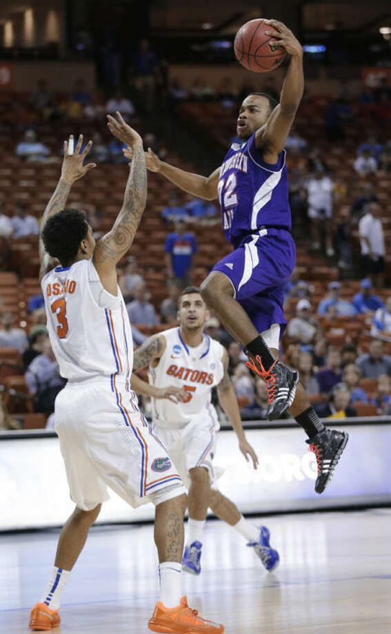 Northwestern State's Brison White, right, drives to the basket over Florida's Mike Rosario (3) during the first half of a second-round game of the NCAA men's college basketball tournament Friday, March 22, 2013, in Austin, Texas. (AP Photo/Eric Gay)
