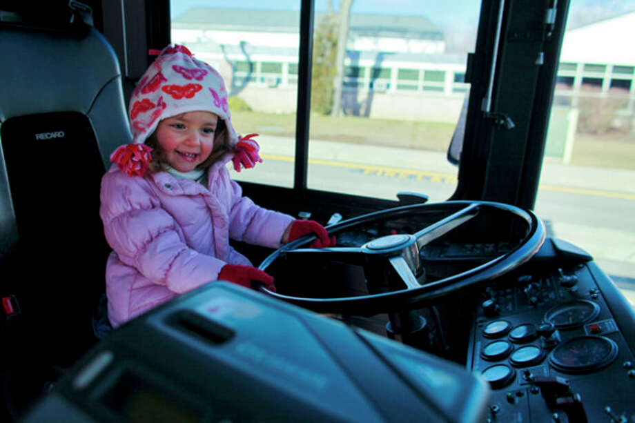 Zoe Malkoun, 3, sits in the drivers seat of a Wheels Bus during Touch a Truck at Coleytown Elementary School in Westport on Saturday, March 23, 2013. (Hour Photo / Chris Palermo) / ©2013 The Hour Newspapers All Rights Reserved.