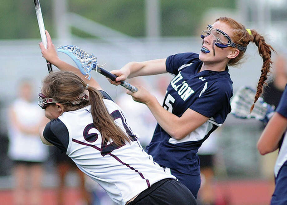 Hour photo/John NashWilton's Shannon Quinlan whips off a shot before East Lyme defender Page Schneider can step in to stop it during Wednesday night's Class M state tournament semifinal game. Wilton rolled into a championship game matchup against New Canaan by routing East Lyme, 18-5.