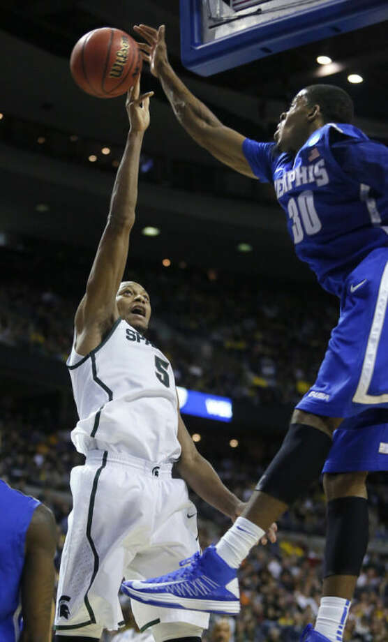 Memphis guard D.J. Stephens (30) blocks a shot by Michigan State forward Adreian Payne (5) in the first half of a third-round game of the NCAA college basketball tournament on Saturday, March 23, 2013, in Auburn Hills, Mich. (AP Photo/Duane Burleson)