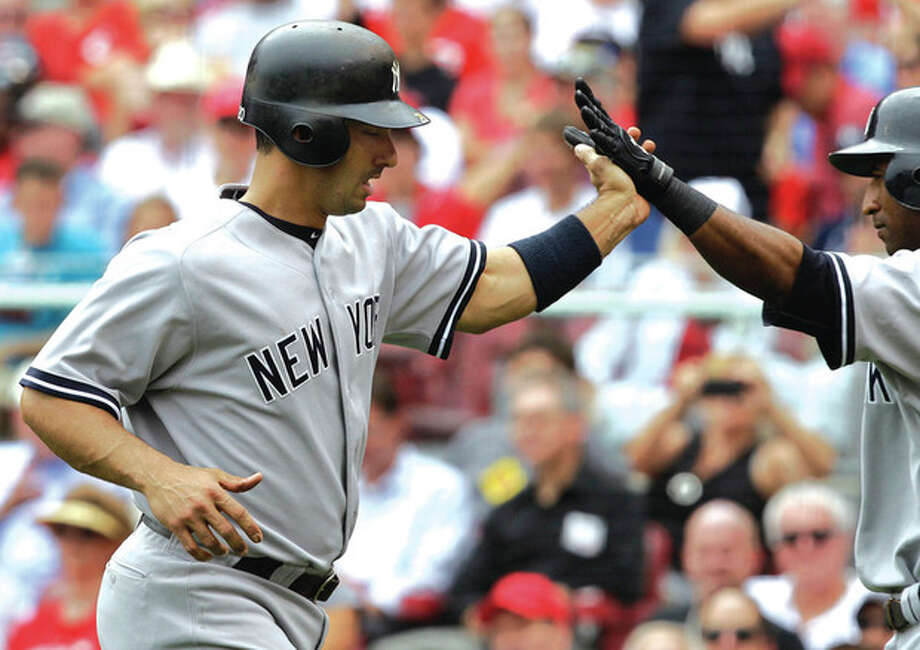 AP photo Jorge Posada, left, is congratulated by New York Yankees Eduardo Nunez after hitting a two-run home run off Cincinnati Reds starting pitcher Mike Leake during the sixth inning of Wednesday afternoonÕs game in Cincinnati. The Yanks beat the Reds, 4-2, but lost the nightcap. / AP