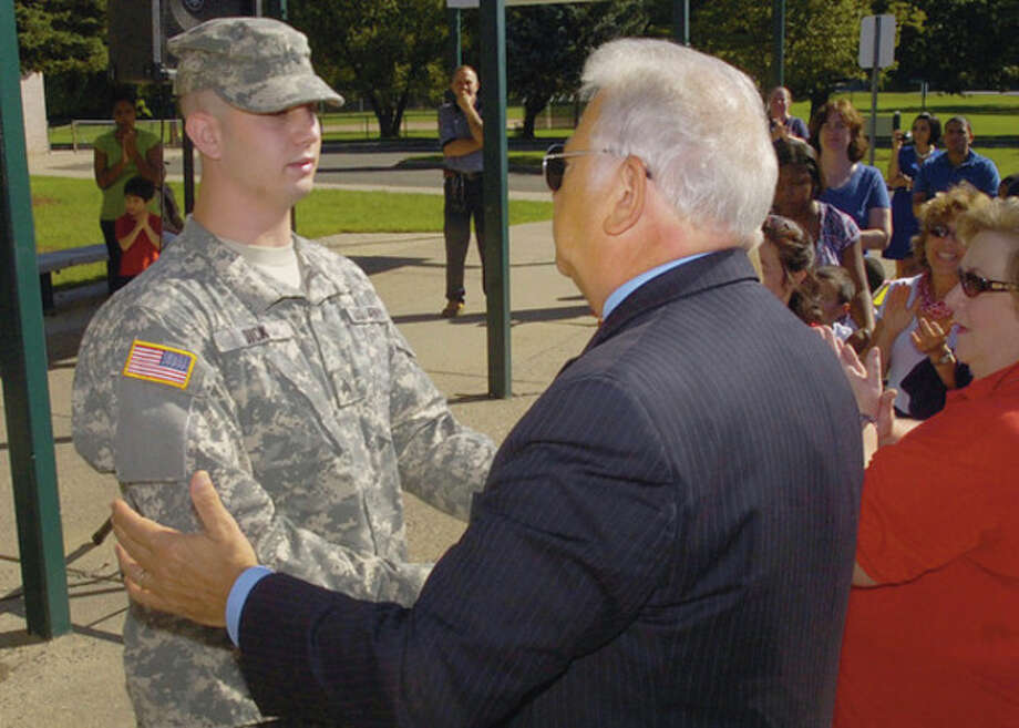 Norwalk Mayor Richard Moccia welcomes Army private Jason Dick, a former student at Fox Run, during a 9/11 commemoration ceremony at Fox Run School Friday. / (C)2011, The Hour Newspapers, all rights reserved