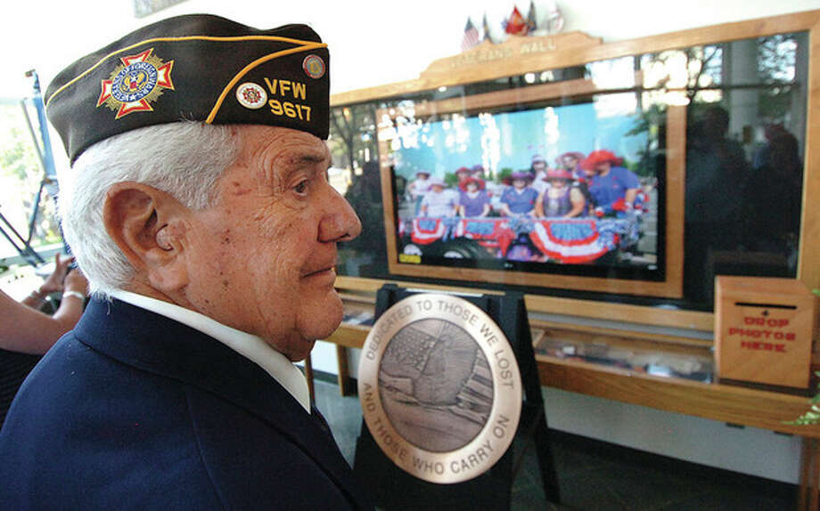 Photo by Alex von KleydorffU.S. Navy veteran Paul Potolicchio watches a video on the new, large TV screen on the remodeled Veterans Wall at the Stamford Government Center. / 2012 The Hour Newspapers